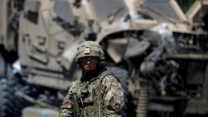A NATO soldier stands at the site of a suicide bomb attack in Kabul, Afghanistan