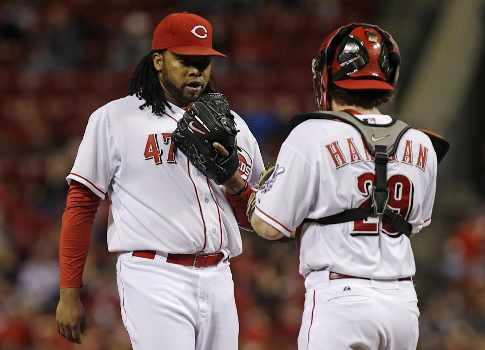 Cincinnati Reds starting pitcher Johnny Cueto (47) talks with catcher Ryan Hanigan (29) in the third inning of a baseball game against the New York Mets, Monday, Sept. 23, 2013, in Cincinnati. (AP Photo/Al Behrman)