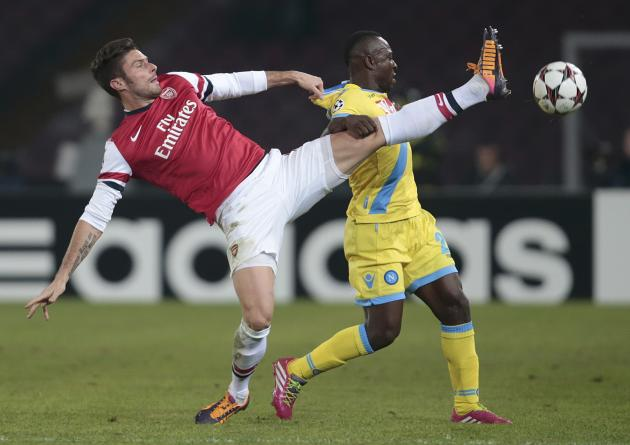 Arsenal's Giroud challenges Napoli's Armero during their Champions League soccer match at San Paolo stadium in Naples