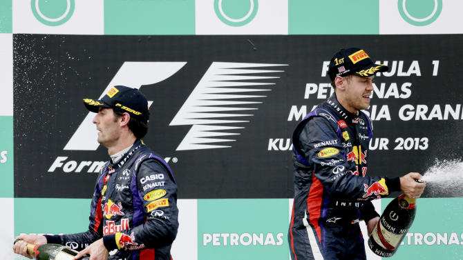 Red Bull driver Sebastian Vettel of Germany, right, and teammate Mark Webber of Australia spray champagne after the awarding ceremony for the Malaysian Formula One Grand Prix at Sepang, Malaysia, Sunday, March 24, 2013. Vettel won the race and Webber finished second. (AP Photo/Andy Wong)