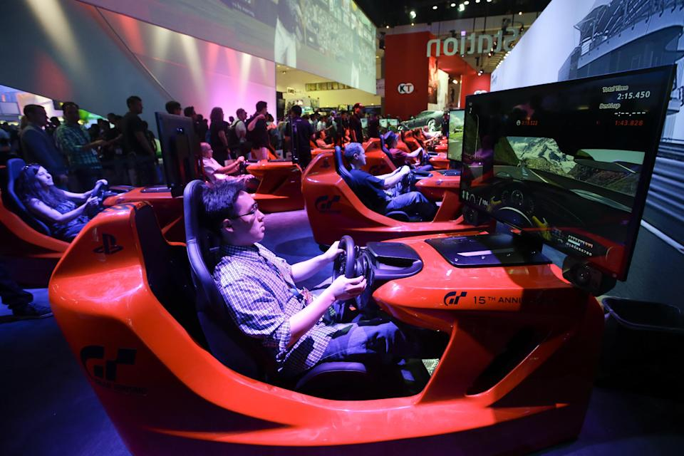 "Show attendees play the popular racing game, ""Gran Turismo,"" in simulators at the Sony booth during the Electronic Entertainment Expo in Los Angeles, Tuesday, June 11, 2013. (AP Photo/Jae C. Hong)"