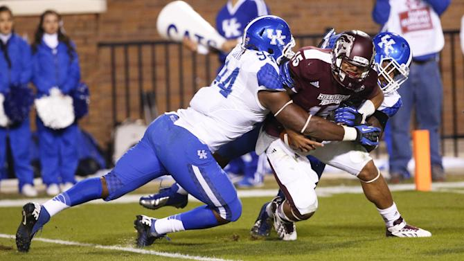 Mississippi State quarterback Dak Prescott (15) is tackled for a loss by Kentucky defensive ends Za'Darius Smith (94) and  Alvin Dupree in the second half of their NCAA college football game at Davis Wade Stadium in Starkville, Miss., Thursday, Oct. 24, 2013. Mississippi State won 28-22