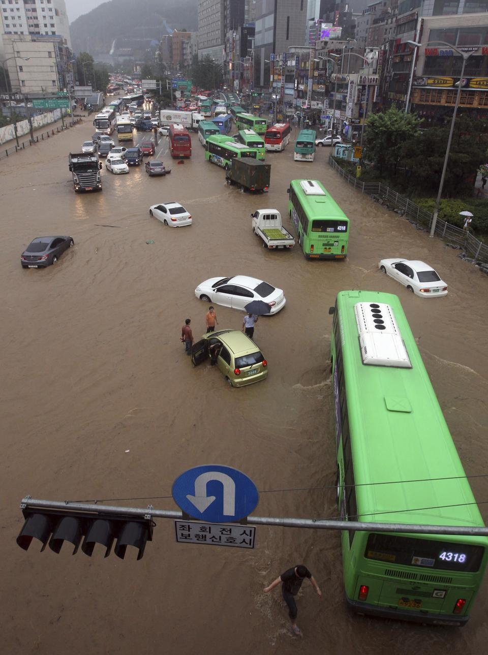 People drive vehicles through a flooded road in Seoul, South Korea, Wednesday, July 27, 2011. Heavy rain sent a landslide barreling into a resort in Chuncheon, a northern South Korean town Wednesday. (AP Photo/Lim Hun-jung) KOREA OUT