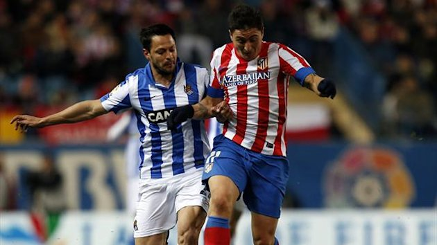 Atletico Madrid's Cristian Rodriguez (R) and Real Sociedad's Alberto de la Bella fight for the ball (Reuters)
