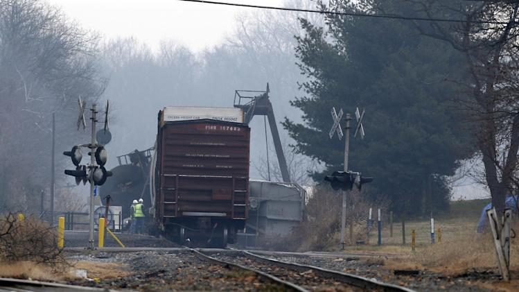 Officials stand next to derailed freight train cars in Paulsboro, N.J., Friday, Nov. 30, 2012, after several tanker cars carrying hazardous materials toppled from a bridge and into a creek. At least one tanker car may contain vinyl chloride, Gloucester County Emergency Management director J. Thomas Butts told WPVI-TV. (AP Photo/Mel Evans)