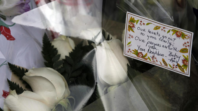 Flowers with a note are placed at a memorial outside the apartment building of the two children allegedly stabbed by their nanny, Saturday, Oct. 27, 2012 in New York.  The 2-year-old son and 6-year-old daughter of a CNBC executive were found dead by their mother in a dry bathtub in the family's Upper West Side apartment Thursday night. The nanny suspected of stabbing the children was in critical condition Friday with apparently self-inflicted injuries. (AP Photo/Mary Altaffer)