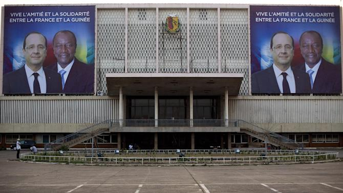 Giant posters featuring French President Francois Hollande and his Guinean counterpart Alpha Conde are displayed on the facade of the People's Palace in Conakry, Guinea, Wednesday Nov. 26, 2014.  Hollande  on Friday will  become the first non-African head of state to visit Guinea since the Ebola crisis began. Hollande will take stock of the response, cheer on heavily-burdened aid providers and help demystify fears about a highly stigmatizing virus. (AP Photo/Jerome Delay)