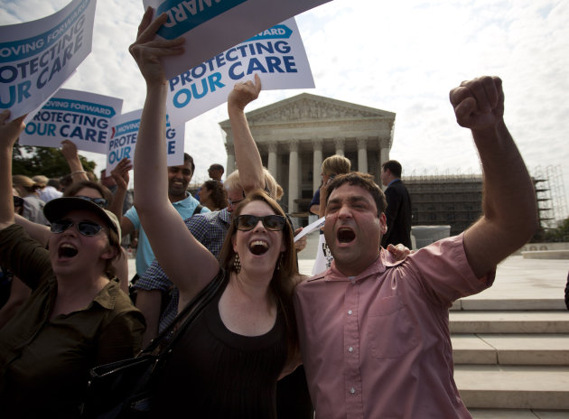 Claire McAndrew of Washington, left, and Donny Kirsch of Washington, celebrate outside the Supreme Court in Washington, Thursday, June 28, 2012, after the courts's ruling on health care.  (AP Photo/Ev