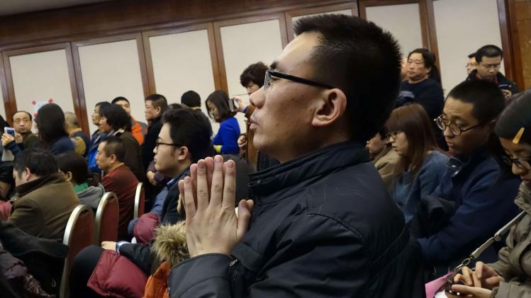 A relative of a passenger of Malaysia Airlines flight MH370 puts his palms together as he prays for his family member at the Lido Hotel in Beijing