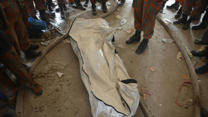 People stand next to a body bag after search and rescue operations on the collapsed garment factory building Monday evening April 29, 2013 in Savar, near Dhaka, Bangladesh. Rescue workers in Bangladesh gave up hopes of finding any more survivors in the remains of a building that collapsed five days ago, and began using heavy machinery on Monday to dislodge the rubble and look for bodies -- mostly of workers in garment factories there. At least 381 people were killed when the illegally constructed, 8-story Rana Plaza collapsed in a heap on Wednesday morning along with thousands of workers in the five garment factories in the building.(AP Photo/Ismail Ferdous)