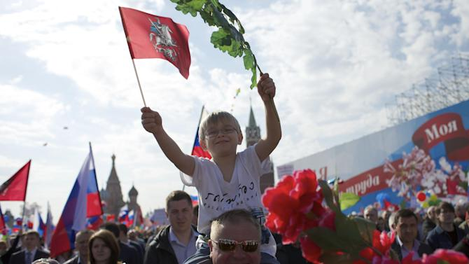 A boy and his father smile as they march with members of Russian Trade Unions during the May Day celebration in Red Square, Moscow, Russia, on Thursday, May 1, 2014. About 100,000 people have marched through Red Square to celebrate May Day, the first time the annual parade has been held on the vast cobblestoned square outside the Kremlin since the fall of the Soviet Union in 1991. (AP Photo/Ivan Sekretarev)