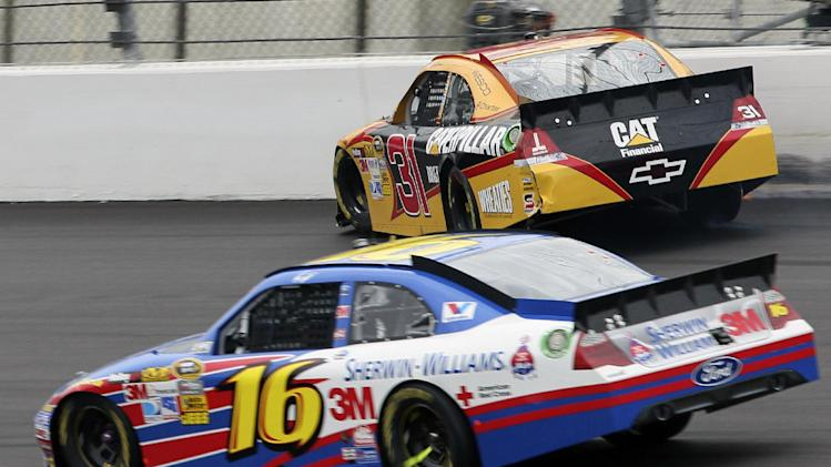 Driver Greg Biffle (16) drives below Jeff Burton (31) who hits the wall during a NASCAR Sprint Cup Series auto race at Kansas Speedway in Kansas City, Kan., Sunday, Oct. 21, 2012. (AP Photo/Colin E. Braley)