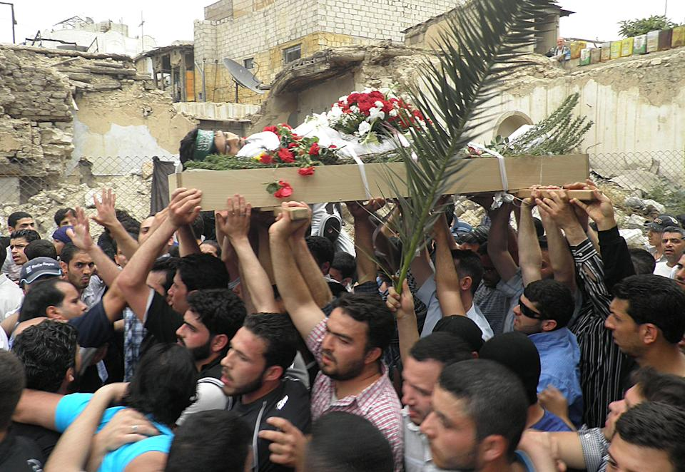 Anti-Syrian regime mourners carry the body of activist Nour al-Zahraa, 23, who was shot by Syrian security forces on Sunday, during his funeral procession, in the Kfar Suseh area, in Damascus, Syria, on Monday, April 30, 2012. (AP Photo)