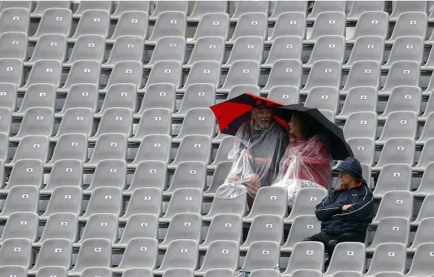 Members of the crowd sit in a stand holding umbrellas during a rain delay before the start of the first day of the first test between England and New Zealand at the University Oval in Dunedin