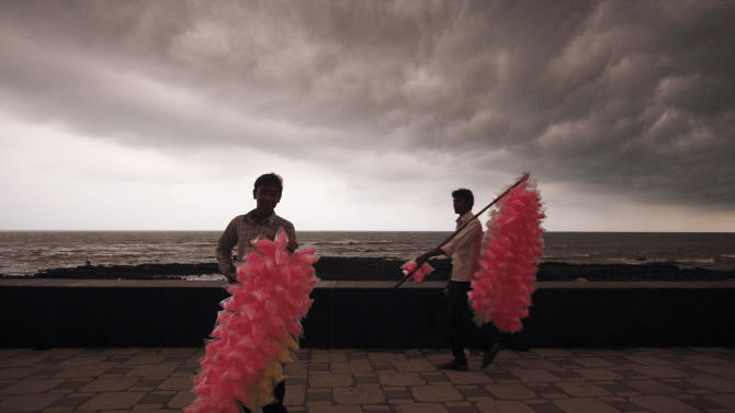 Street vendors carrying cotton candy wait for customers as storm clouds gather over horizon in Mumbai