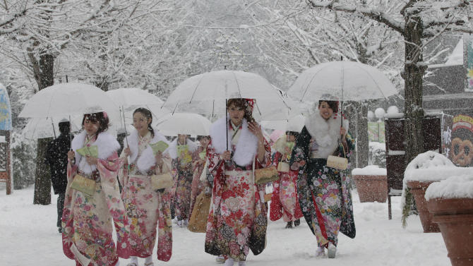 Dressed in Japanese kimonos, Japanese youths who have turned or will turn 20-year-old this year, the traditional age of adulthood in Japan, walk in the snow following a Coming of Age ceremony at an amusement park in Tokyo Monday, Jan. 14, 2013. (AP Photo/Shizuo Kambayashi)