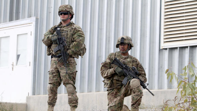 FILE - In this Nov. 28, 2012 file photo, U.S. soldiers with stand guard as they watch the transfer ceremony of security responsibilities from NATO troops to Afghan security forces in Qalat, Zabul province south of Kabul, Afghanistan. The debate over how many U.S. troops will remain in Afghanistan after 2014 comes down to risk. Leaving too few troops in place could stall progress for Afghan security forces. But keeping too many troops there might prolong Afghanistan's dependence on the U.S. military and NATO. (AP Photo/Allauddin Khan, File)