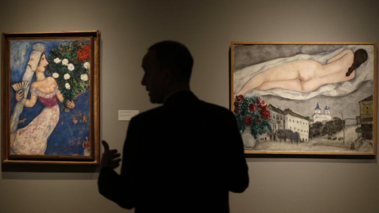 "In this photo taken Wednesday, Feb. 13, 2013, museum curator Olivier Meslay talks about paintings by artist Marc Chagall included in the ""Chagall: Beyond Color,"" exhibit during a preview at the Dallas Museum of Art in Dallas. This will be the only U.S. venue to host the exhibit that opens to the public on Sunday. (AP Photo/LM Otero)"