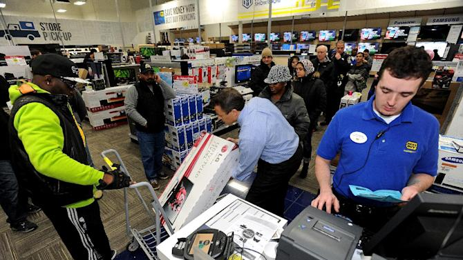 FILE - In this Nov. 29, 2013, file photo, Best Buy employee Christopher Gervais, right, rings up a 32-inch LED TV in Dunwoody, Ga. Sales at U.S. stores dropped 3.1 percent to $42.7 billion for the week that ended on Sunday, Dec. 22, 2013, compared with the same week last year, according to ShopperTrak, which tracks data at 40,000 locations. (AP Photo/David Tulis, File)