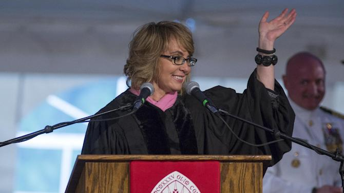Former U.S. Rep. Gabrielle Giffords and her husband, retired space shuttle Commander Mark Kelly, background right, acknowledge the crowd after delivering the commencement address in two parts, during the 153rd Commencement at Bard College, Saturday, May 25, 2013, in Annandale-on-Hudson, N.Y. Giffords also received an honorary degree. (AP Photo/Philip Kamrass)
