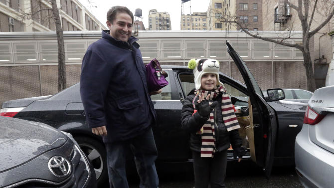 Mike Marino, left, accompanies Siena Marino, who usually rides a school bus to Public School 9, as they arrive for school by car on New York's Upper West Side, Wednesday, Jan. 16, 2013.  More than 8,000 New York City school bus drivers and matrons went on strike over job protection Wednesday morning, leaving some 152,000 students, many disabled, trying to find other ways to get to school. (AP Photo/Richard Drew)