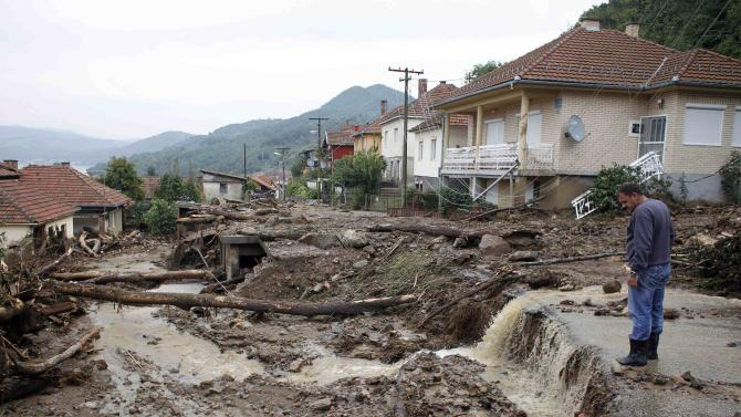 Man inspects the damage produced by heavy floods in Tekija village