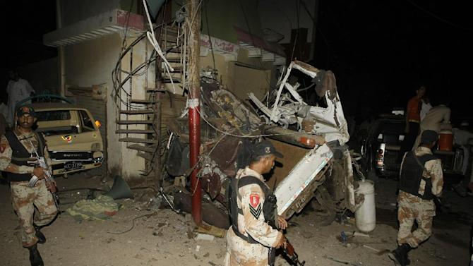 Pakistani para-military troops cordon off the area of an explosion in Karachi, Pakistan Friday, April 26, 2013.  A bomb planted near the office of a political party threatened by the Taliban has killed many people in southern Pakistan, police said. (AP Photo/Fareed Khan)