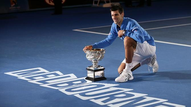 Novak Djokovic of Serbia poses with the trophy after defeating Andy Murray of Britain in the men's singles final at the Australian Open tennis championship in Melbourne, Australia, Sunday, Feb. 1, 2015. (AP Photo/Vincent Thian)