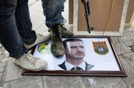 Syrian rebels stand on a picture of President Bashar al-Assad in the northern city of Aleppo. Fighting raged in Aleppo as rebels doggedly resisted a regime onslaught launched in the northern city a month ago