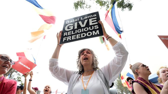 A woman holds a sign during a protest outside the Bren Events Center where The Dalai Lama is speaking today at the University of California, Irvine