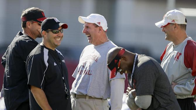 Nebraska head coach Bo Pelini, center, jokes with members of his staff, from left: wide receivers coach Rich Fisher, defensive coordinator John Papuchis, secondary coach Charlton Warren, and assistant coach Ross Els, during team practice in Lincoln, Neb., Wednesday, Aug. 13, 2014