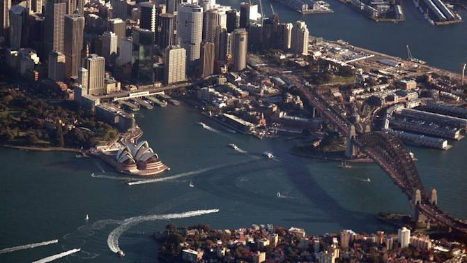 The Sydney Harbour Bridge casts a shadow next to the Sydney Opera House and CBD as boats make their along the harbour