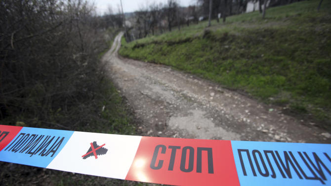A police tape is seen on the road near a house in village of Velika Ivanca, Serbia, Tuesday, April 9, 2013. A 60-year-old man gunned down 13 people, including a baby, in a house-to-house rampage in a quiet village on Tuesday before trying to kill himself and his wife, police and hospital officials said. (AP Photo/Darko Vojinovic)
