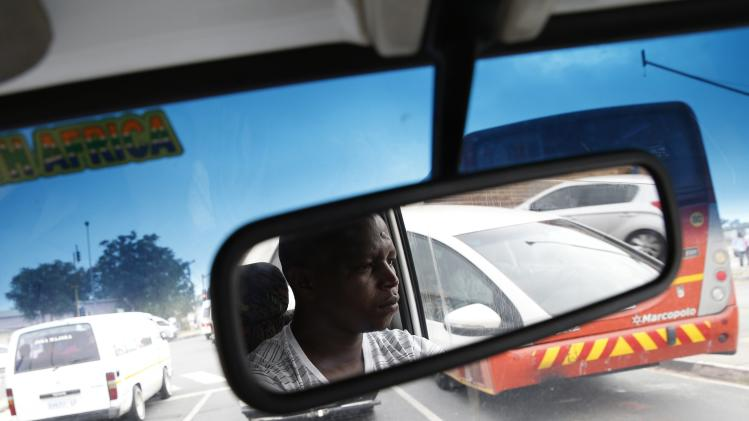 Minibus taxi driver Zakes Hadebe is reflected in his rearview mirror during his first run of the day ferrying passengers from Soweto township to central Johannesburg
