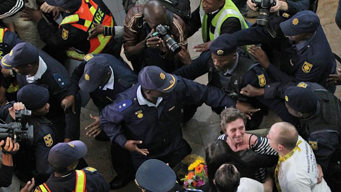 South African Deborah Calitz, reacts as she greets a family member upon their arrival with partner Italian Bruno Pelizzari, bottom right, whilst escorted by police officers at the OR Tambo International Airport in Johannesburg, South Africa on Wednesday June 27, 2012. The South African and Italian couple were held hostage for 20 months after being kidnapped in October 2010 from a yacht by Somali pirates. (AP Photo/Themba Hadebe)