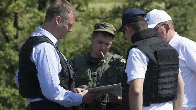 Alexander Hug, deputy head of the OSCE mission to Ukraine, left, his colleagues and a pro-Russian rebel, 2nd left, examine a map as they try to estimate security conditions outside the city of Donetsk, eastern Ukraine Wednesday, July 30, 2014. (AP Photo/Dmitry Lovetsky)