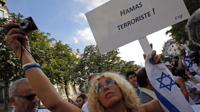 """A woman holds an Israeli flag and a placard reading """"Hamas Terrorist"""" during a gathering in front of the Israeli Embassy in Paris, France, Thursday, July 31, 2014. French police were bracing for the first major pro-Israel rally in Paris since the start of the Gaza war amid persistent reports that a small Jewish group implicated in violence at pro-Gaza rallies could be banned. (AP Photo/Francois Mori )"""