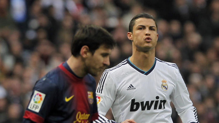 Real Madrid's Cristiano Ronaldo from Portugal, right, and FC Barcelona's Lionel Messi from Argentina gesture during a Spanish La Liga soccer match at the Santiago Bernabeu stadium in Madrid, Spain, Saturday, March 2, 2013. (AP Photo/Andres Kudacki)