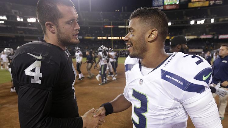 Oakland Raiders quarterback Derek Carr (4) shakes hands with Seattle Seahawks quarterback Russell Wilson (3) after an NFL preseason football game in Oakland, Calif., Thursday, Aug. 28, 2014. The Raiders won 41-31