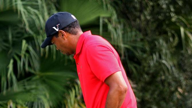 Tiger Woods limps after hitting from the 12th tee during the final round of the Cadillac Championship golf tournament, Sunday, March 11, 2012, in Doral, Fla. Woods withdrew from the tournament. (AP Photo/Wilfredo Lee)