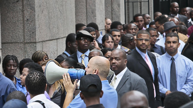 FILE - In this Thursday, Aug. 8, 2013, file photo, applicants listen to a speaker's bull horn instructions for attending a combined Metropolitan Transportation Authority (MTA) and Harlem Week job and career fair in New York. The Labor Department reports on the number of Americans who applied for unemployment benefit the first week of November on Thursday, Nov. 7, 2013. (AP Photo/Bebeto Matthews, File)