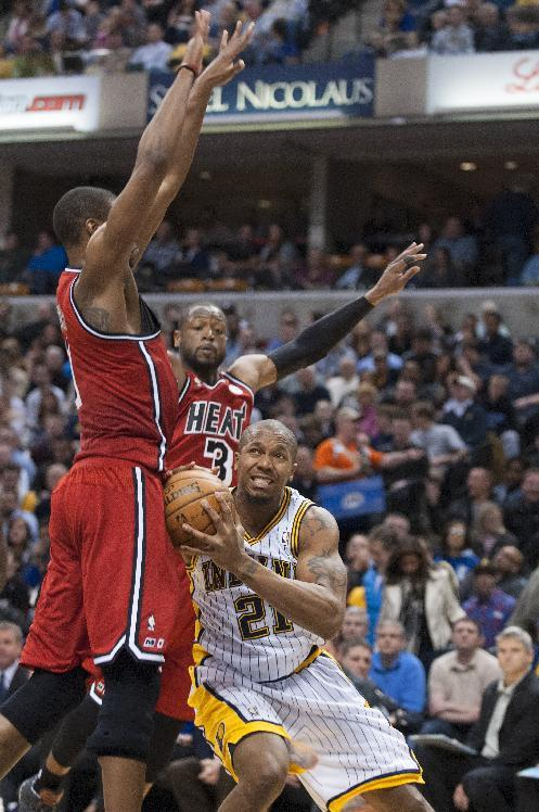 Indiana Pacers' David West (21) drives the ball past the defense of  Miami Heat's Dwyane Wade (3 and Chris Bosh (1) during the second half of an NBA basketball game in Indianapolis, Friday, Feb. 1, 2013. The Pacers defeated the Heat 102-89. (AP Photo/Doug McSchooler)