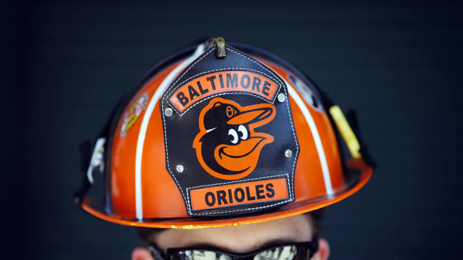 Wes Roberts, of Whiteford, Md., poses in a Baltimore Orioles-themed fireman's helmet before an opening day baseball game between the Orioles and the Boston Red Sox, Monday, March 31, 2014, in Baltimore. (AP Photo/Patrick Semansky)