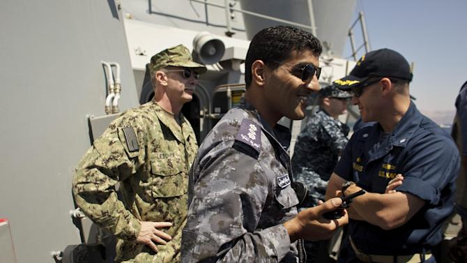 U.S. Rear Admiral William Lescher, left, Jordanian Navy Capt. Anas Saleh, center, and Commander Bo Johns, right, observe joint maneuvers with the Jordanian Navy aboard the USS Stockdale in the Gulf of Aqaba, Jordan as part of Eager Lion, a multinational military exercise, Tuesday, June 18, 2013. Under the watchful eye of stern-faced American advisers, hundreds of U.S.-trained Jordanian soldiers are holding war games that could eventually form the basis of an assault in Syria. There is fear of spillover from the Syrian war in this U.S.-allied kingdom, and the potential for a Jordanian role in securing Syria's chemical stockpiles should Bashar Assad's regime lose control. (AP Photo/Maya Alleruzzo)