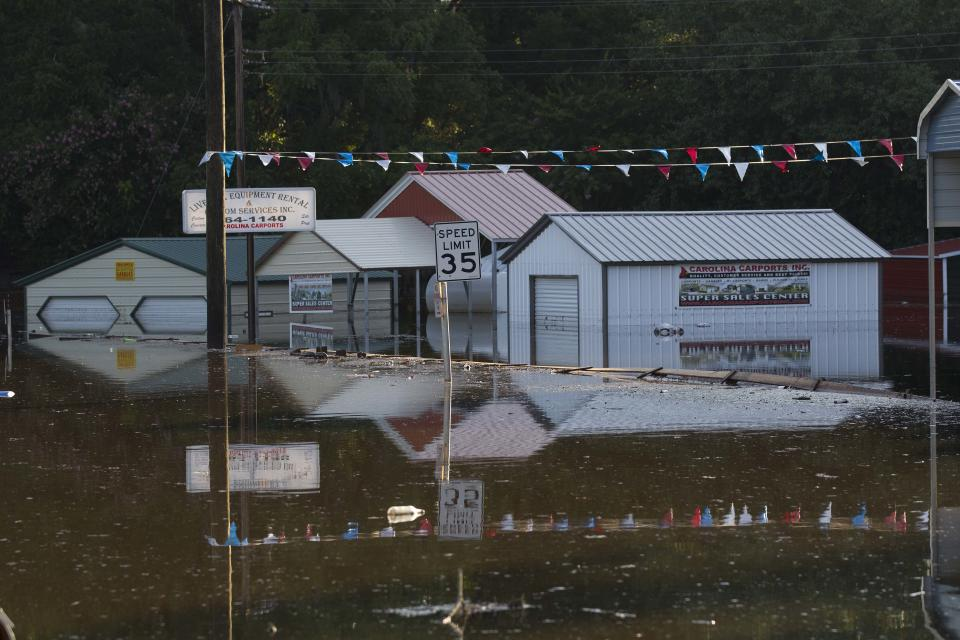 Flood water surrounds businesses in Live Oak Fla., Wednesday, June 27, 2012. Dozens of homes and much of the downtown area was flooded by torrential rains from Tropical Storm Debby.   (AP Photo/Dave Martin)