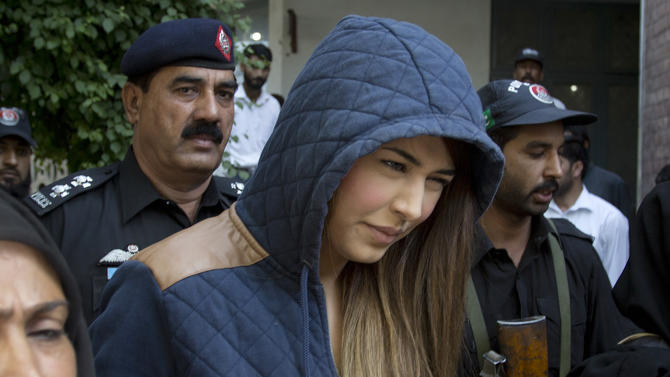 In this photo taken on Monday, June 1, 2015, police officers escort Pakistan's supermodel Ayaan Ali to a court under tight security in Rawalpindi, Pakistan. A government lawyer says a Pakistani court has rejected a bail plea from top model Ayaan Ali, who has been held since March after being caught trying to fly to Dubai with half a million dollars in cash stashed in her luggage. (AP Photo/B.K. Bangash)