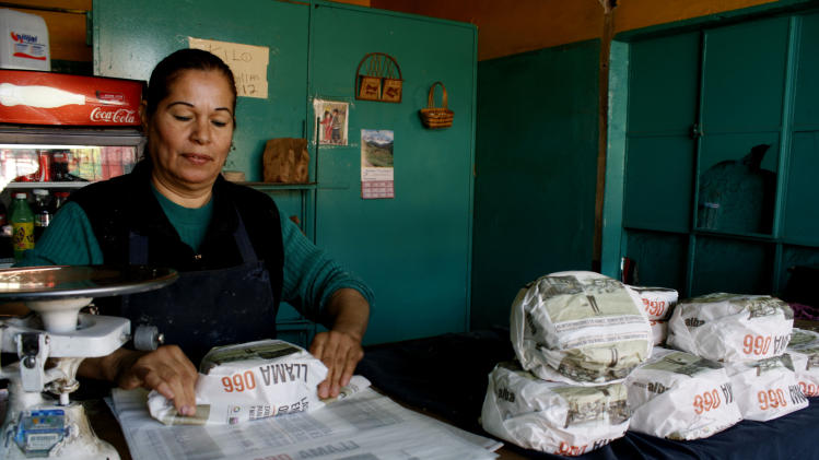 Esperanza Lozoya wraps tortillas packaged with advertisements that ask for help to find missing women and children, at the Hermanos Escobar Tortilla shop in the northern border city of Ciudad Juarez, Mexico, Tuesday Nov. 13, 2012. At least three dozen tortilla shops have joined in the Chihuahua state campaign to print appeals for help on thin paper wrappers that shopkeepers use to wrap up a pound or two of hot tortillas at a time. (AP Photo/Raymundo Ruiz)