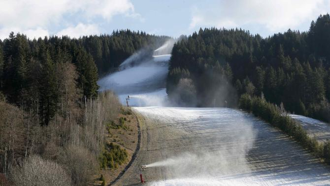 Artificial snow making machines operate on grass-covered slopes at the ski station at Les Gets in the French Alps
