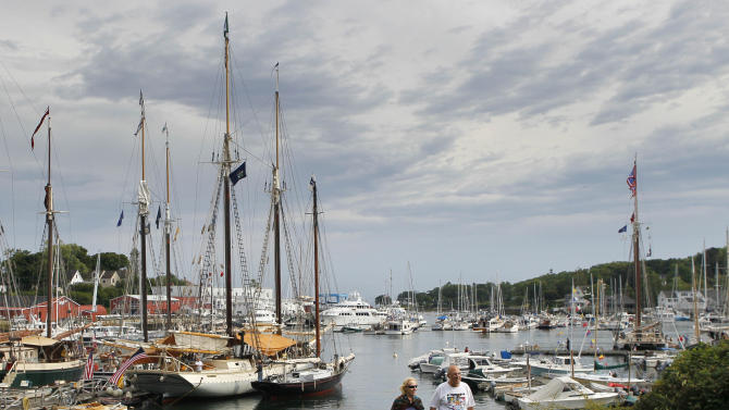 In this photo made Friday, Aug. 31, 2012, a couple strolls through a park by the harbor in Camden, Maine. The small coastal town is often cited in lists of best retirement places to move for people interested in cooler climates. (AP Photo/Robert F. Bukaty)