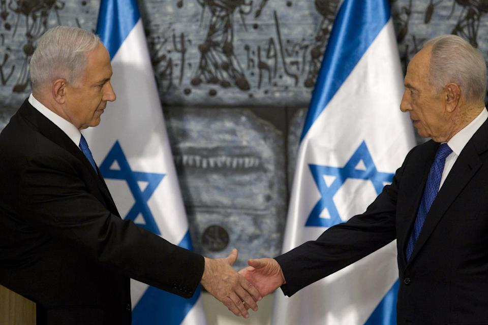 Israeli Prime Minister Benjamin Netanyahu, left, shakes hands with Israeli President Simon Peres during a brief ceremony in the president' Jerusalem residence Saturday Feb. 2, 2013.  Israel's president has asked Netanyahu to form the next government, and Netanyahu says he wants to advance peace talks with the Palestinians. (AP Photo/Jim Hollander, Pool)